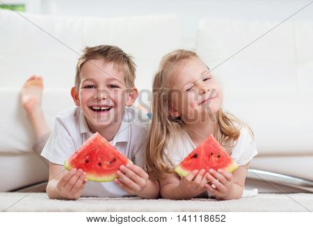 Happy little children eating watermelon at home