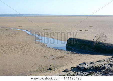 A sewage pipe on a sandy beach