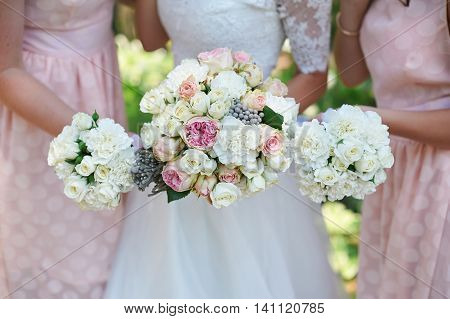 Bride is holding beautiful bright wedding bouquet.