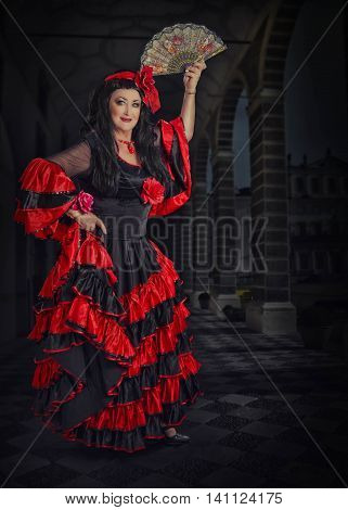 Vertical portrait of mature female dancer posing with fan on stage.  Black haired woman wears red and black flamenco floor-length gown with frills