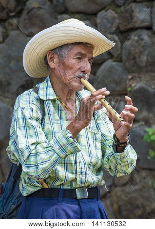 PANCHIMALCO EL SALVADOR - MAY 08 : A Salvadoran man plays flute during the Flower & Palm Festival in Panchimalco El Salvador on May 08 2016