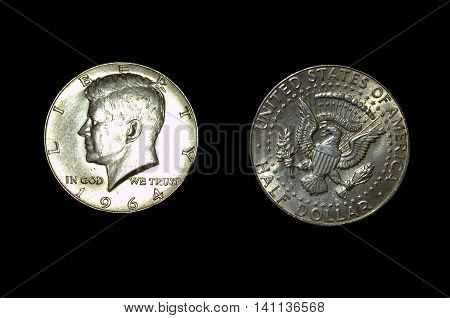 1964 Kennedy Half Dollar, front and back, against isolated background.