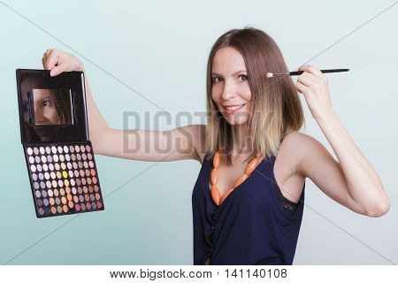 Woman stylist applying eyeshadow with professional makeup palette and brush. Girl beautyfying eye eyelid. Make up makeover concept.