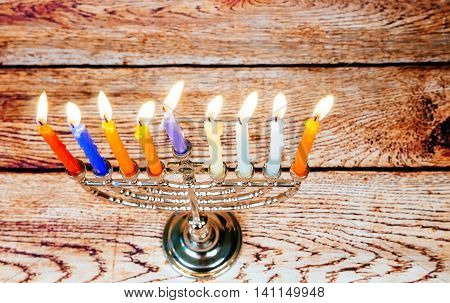 low key image of jewish holiday Hanukkah with menorah traditional Candelabra and wooden dreidels spinning top . glitter overlay