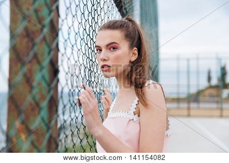 Beautiful young woman standing and posing outdors near chain link fence