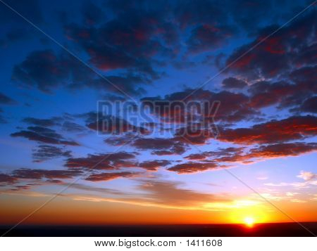 Sunrise With Red Clouds And Blue Skies