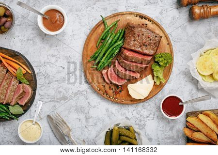 Sliced medium rare grilled steak on a wooden board on a white surface with different vegetables and sauces top view