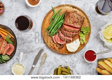 Sliced medium rare grilled steak on a wooden board on a white surface with different vegetables sauces and red wine top view