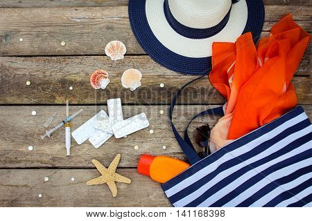 Summer women's beach accessories for your sea holiday and pill on old wooden background. Concept of medication required in journey