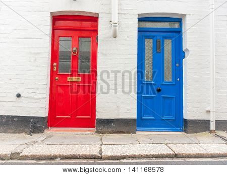 Two traditional style doors together different colors facing the street