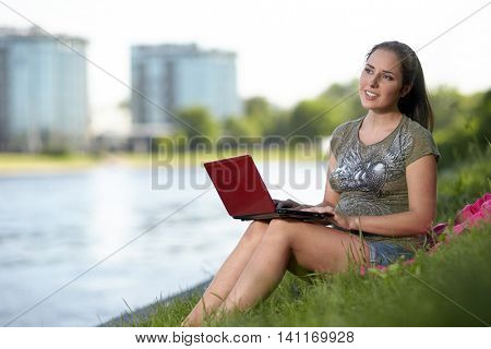 Young pregnant woman sits on a grass in the park with the laptop.