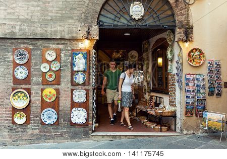 SIENA ITALY - JUNE 29 2016: Tourists visiting traditional art and souvenir shop in old town of Siena Italy