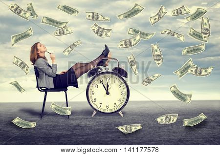 Happy young business woman sitting on a chair under a money rain
