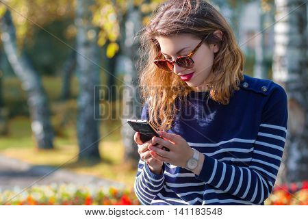 Happy young woman using a mobile phone outdoors in the fall.