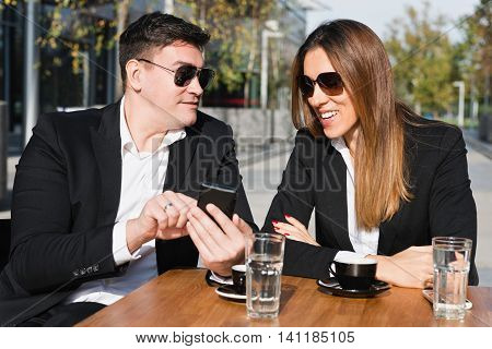 Casual business talk over coffee, outdoors in caffee