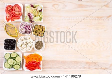 Ingredients for greek salad in bowls with copy space, top view