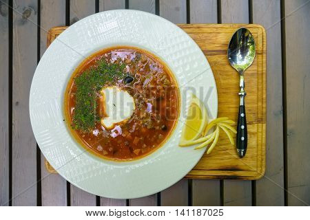 Russian traditional thick meat soup solyanka served on wooden table