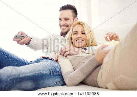 Happy young couple lying on the sofa at home with popcorn watching TV. They are laughing and watching a movie or television.
