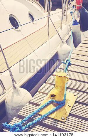 Yacht Moored To A Yellow Bollard In Marina.