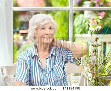 Beautiful senior woman sitting in her winter garden , one hand on her neck, in the background the garden