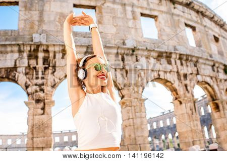 Young sports woman with headphones and sunglasses stratching after the training near the ancient amphitheatre in Pula city