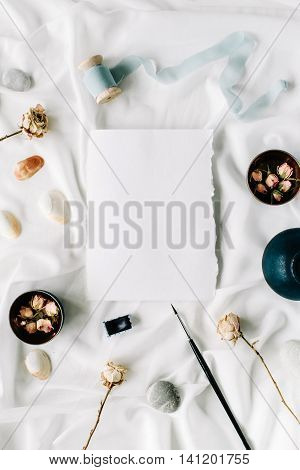 Flat lay wedding invitation card blank dry roses brush stones shells spool with ribbon menu carte on white textile. Overhead view.