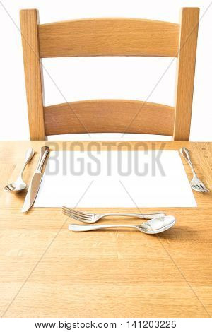 Chair and place setting and on a wooden table with knife fork soupspoon and desert cutlery