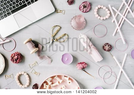 Flat lay top view office table desk. Workspace with laptop purple candles spool set decor golden scissors and clips on grey concrete background.