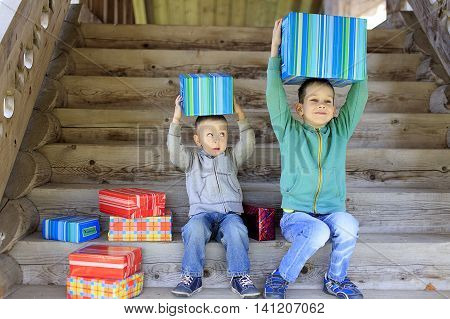 children enjoy gifts. Two cute boys put gift boxes on heads and having fun. different gifts to the children. envy, comparison of gifts