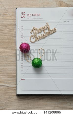 Diary open on the 25th of December decorated with baubles and merry christmas