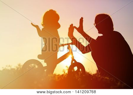 father and little daughter riding bike at sunset sky