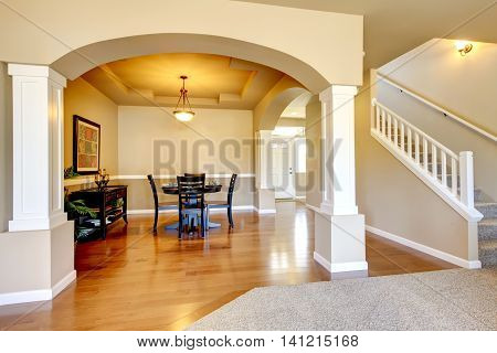 Spacious Dining Room With White Columns And Beige Tray Ceiling.