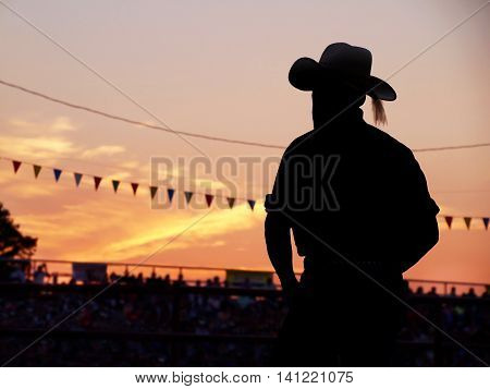 A silhouetted man in a cowboy hat stands in the bleachers watching a rodeo at sunset.
