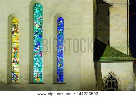 ZURICH SWITZERLAND - DECEMBER 25 2015: The exterior of the Fraumunster (Women Minster) Church at night with its stained glass windows (by Marc Chagall) in Zurich Switzerland