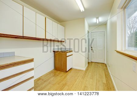 Bright Laundry Room Interior With Cabinets And Hardwood Flooring.