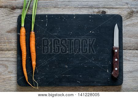Cooking food, recipe mock up. Fresh organic carrots with green tops and small kitchen knife on black chopping board. Top view. Copy space for text.
