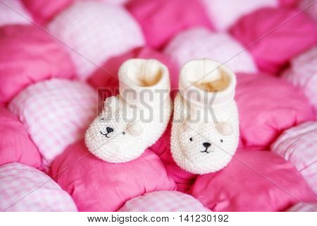 Cute small white baby booties on pink blanket. Pregnancy concept