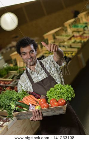 Grocery Clerk Working In Produce Aisle Of Supermarket Store
