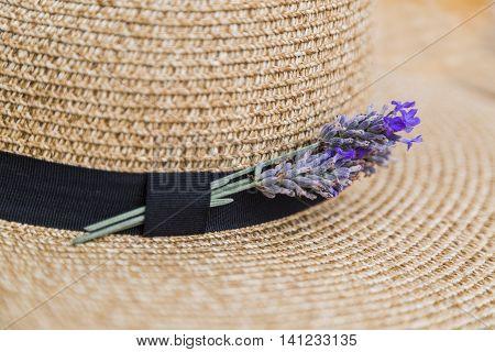 Twig of fresh purple fragrant lavender inserted in black ribbon on wicker straw flaxen hat