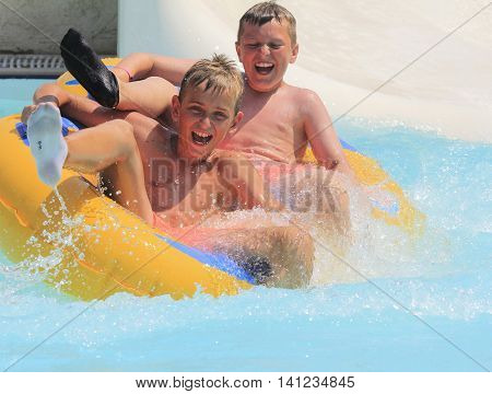 Rhodes Greece-August 12016:The group of boys on the rafting slide in the Water park.Rafting slide is one of many popular game for adults and children in park.Water Water Park is located on the island of Rhodes in Greece and one of the most largest in Euro