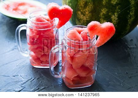 Watermelon in Mason jars decorated with watermelon slices curved like heart symbols.