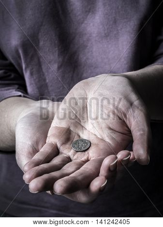 Closeup of poor begging woman hands holding a coin