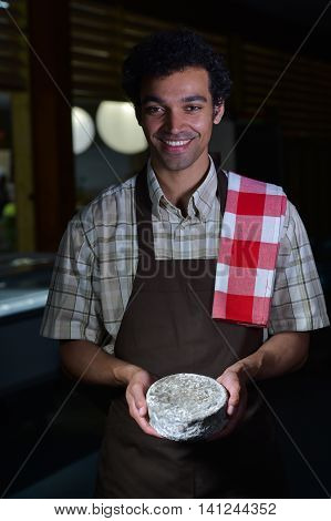 French tomme cheese in the hands of a cheesemaker Studio shoot