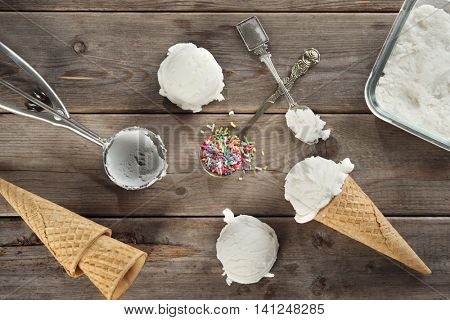 Top view vanilla ice cream and waffle cone with utensil on wood background.