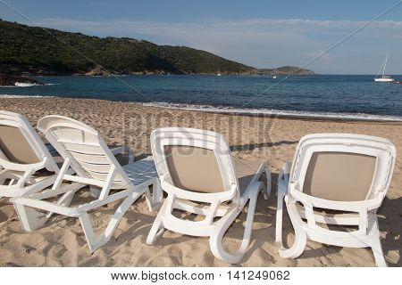 Deckchairs on the beach with bright sun and waves