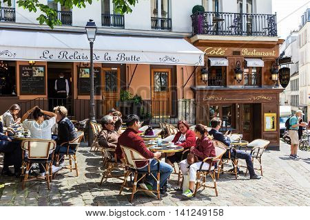 Paris France - June 28 2016: A traditional restaurant in Paris in the Butte Montmartre. Parisians and tourists enjoy food and drinks under the sun. Montmartre area is most popular destinations in Paris has lots of cozy cafes restaurants bistros night club