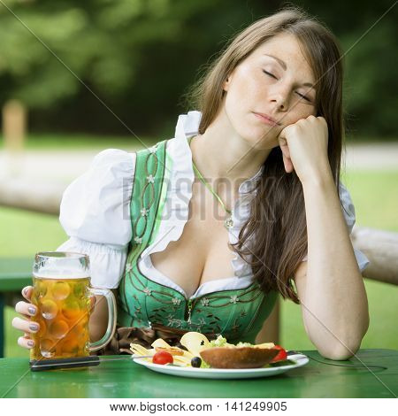 young woman in dirndl sleeping at table in beer garden and holding a beer mug