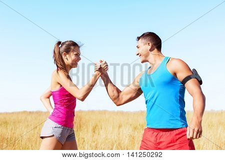 Fitness sport running couple celebrating cheerful and happy giving high five energetic and cheering. Runner couple having fun after trail cross-country running training. Asian woman, Caucasian man