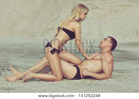 Woman flirting with a man on the beach she touches his muscular body.
