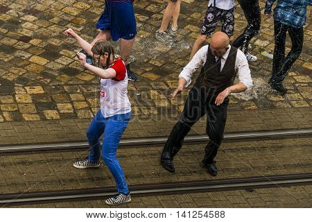 Lviv Ukraine - May 2 2016: Celebration pouring water on Monday after Easter by the town hall. Bald men dances with wet girl